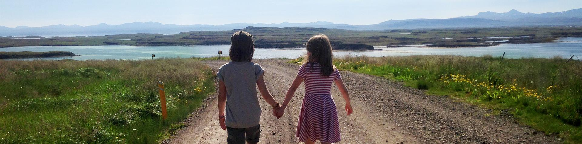 Family holidays in Iceland: Boy and a girl holding hands on a summer family holiday to Myvatn, northern Iceland.