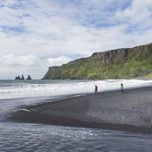 Escorted tour of Reykjavik and south coast of Iceland: couple strolling on the black beach Reynisfjara, south of Iceland.